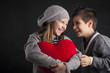 Couple of kids having fun with red heart over black background.