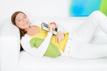 junge frau entspannt auf dem sofa mit einem buch