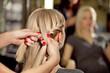Hairdresser make French braid   in beauty salon.