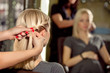 Hairdresser make French braid   in beauty salon.