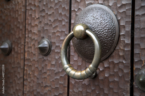 Old medieval brass knocker on antique dark wooden door