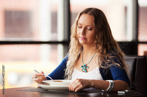 Beautiful woman eating a soup at restaurant