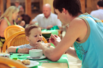 At summer restaurant the father feeds with a spoon of the small