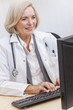 Senior Female Doctor With Stethoscope at Desk & Computer