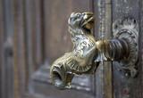 Old golden door handle unique on a wooden door