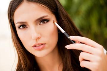 portrait of beautiful  brunette girl making up