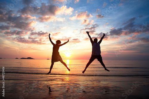Young couple in a jump on the sea beach at sunset.