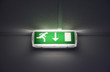 Green exit sign with running man on the wall