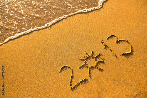 2013 written in sand on beach texture (soft wave of the sea)