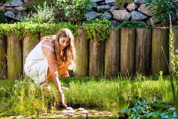 Woman sitting at pond in her garden
