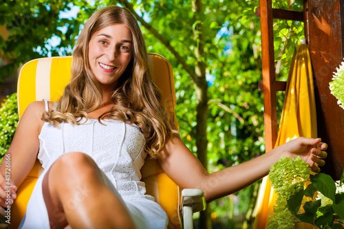 Woman tanning in the sun in her garden