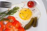 Fried eggs with cucumbers, tomato, pepper and greens