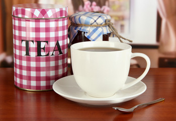 Jar and cup of tea on table in room