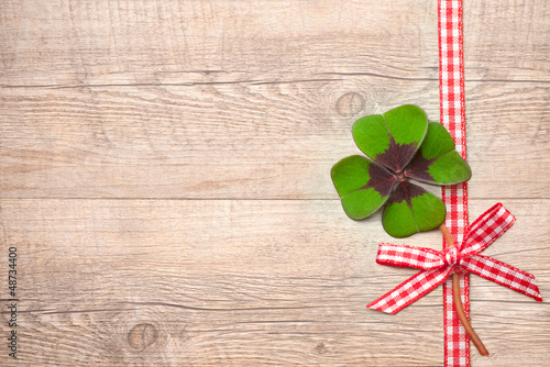 Four leaf clover over wooden background