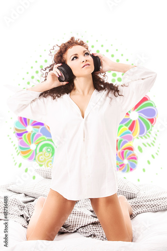 Curly woman with white lingerie and headphones in the bed