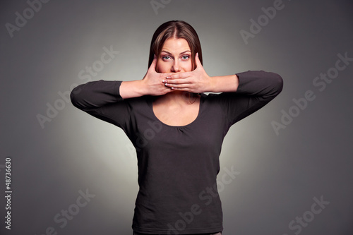 woman holding hands over her mouth
