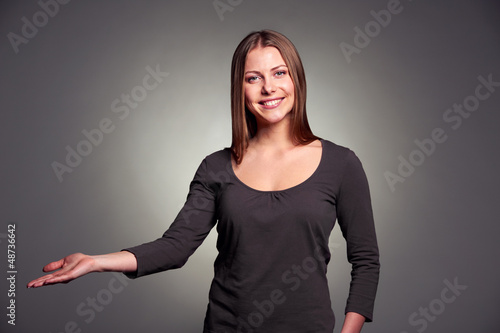 woman holding open palm over dark background