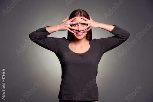woman looking through her fingers
