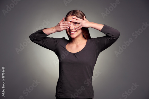 woman peeping through her fingers