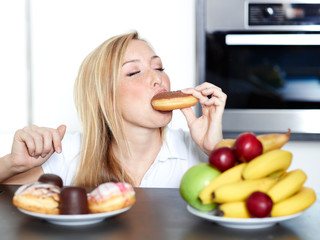 Pretty woman choosing between fruits and sweets, enjoys a donut