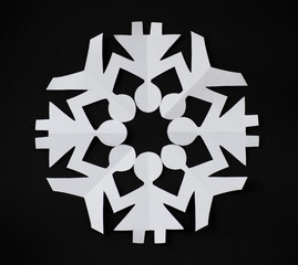 PAPER SNOWFLAKE CUT AS PEOPLE HOLDING THEIR HANDS