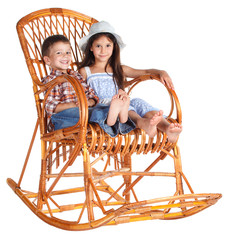 Two kids sitting in the rocking chair
