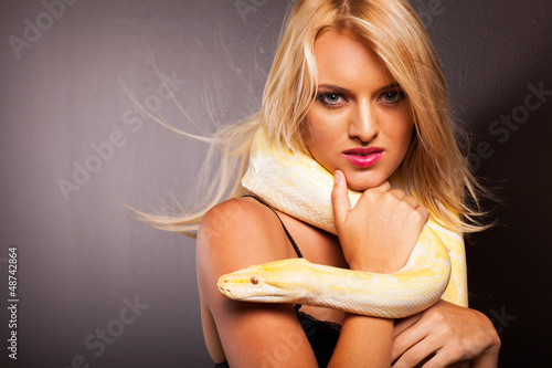 attractive blonde woman holding python on her shoulder