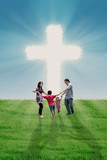 Christian family at bright Cross