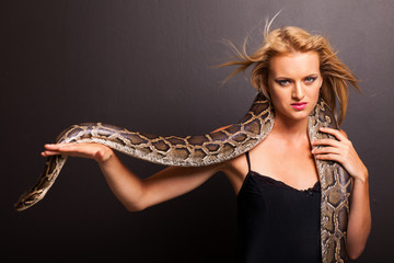 sexy young woman holding a python on black background