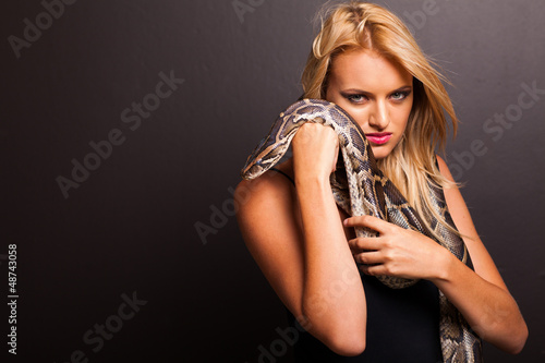 beautiful young blonde woman holding python