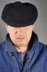 Unshaved man in a black cap
