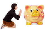 Kneeling woman praying in front of the piggy bank