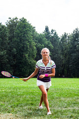 beautiful and young woman playing badminton
