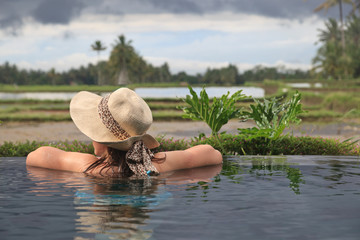 woman in infinity pool enjoying rice fields view