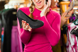 Woman is buying shoes for her Tracht or dirndl in a shop