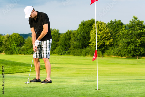 Young golf player on course putting to the hole