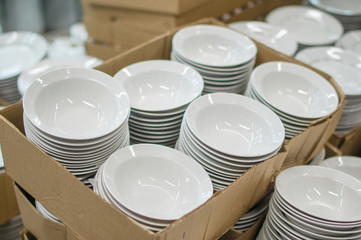 Bunch of white soup plates in boxes in supermarket