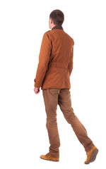 Back view of walking  businessman in jeans and jacket