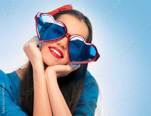 Portrait of a beautiful woman in blue with heart shaped glasses