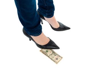 Woman in stilettos standing over ten dollar note