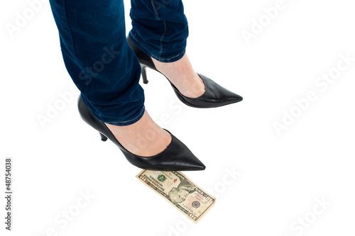 Woman in stilettos standing over ten dollar note