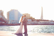bride and groom posing on waterfront in the urban landscape