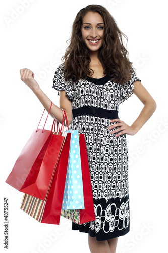 Shopaholic brunette carrying vibrant color bags