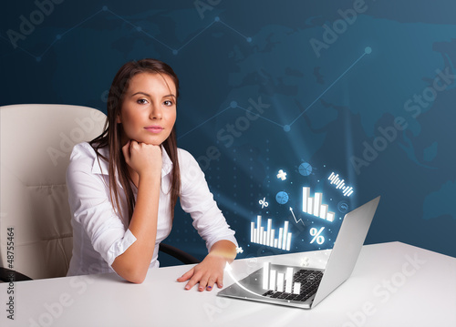 Pretty woman sitting at desk and typing on laptop with diagrams
