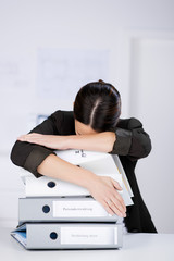 müde geschäftsfrau schläft auf aktenordnern