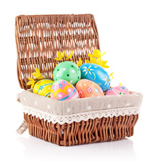 easter eggs in basket with yellow flowers isolated on white