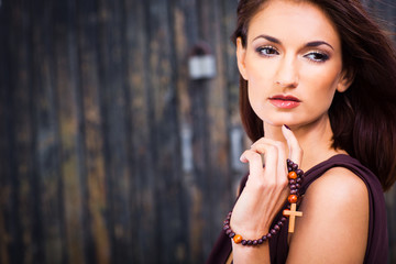 beautiful girl with christian beads against old wooden wall