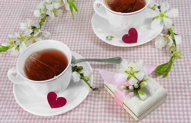 Tazas de té rojo, con cajita y corazones.