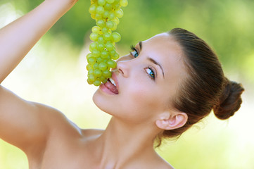 woman bites off from grape bunches