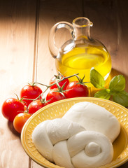 mozzarella cheese with olive oil and tomatoes on wooden table